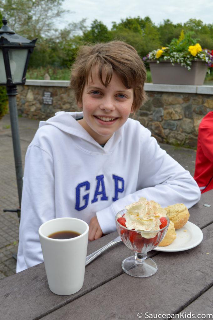 Irish National Heritage Park Ringfort Stayover review - by Saucepan Kids - Anna enjoying strawberries and scone