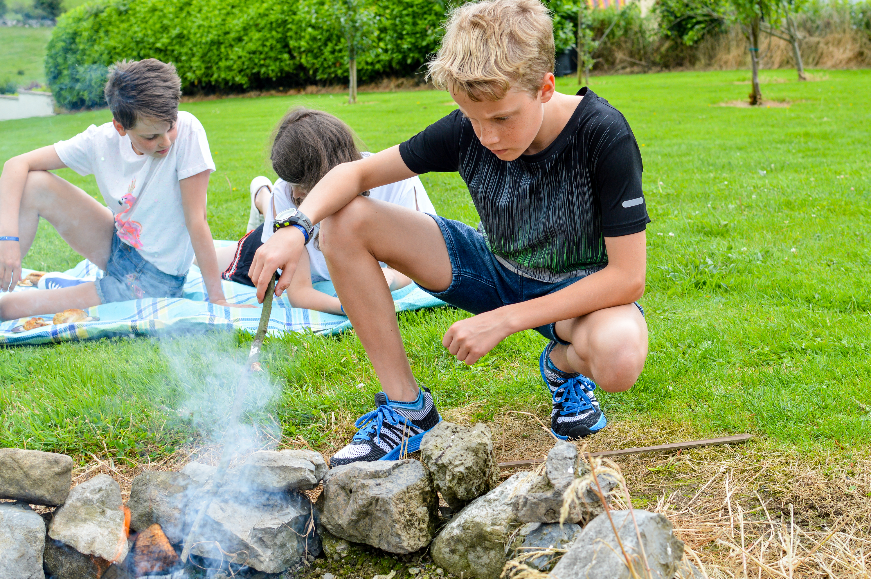 Enjoying a summer camp fire wearing their Marks and Spencer t-shirts and shorts