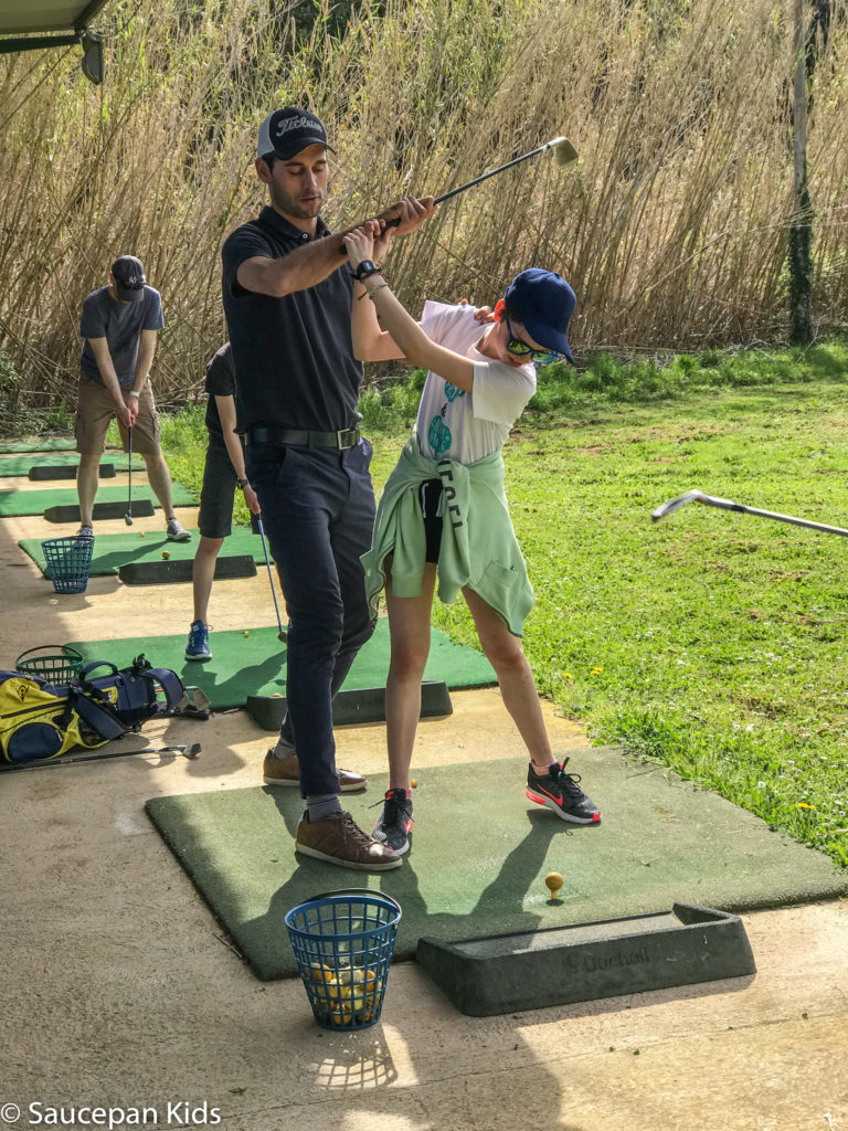 thing-to-Family Friendly things to do in Costa Brava with Saucepan Kids - Catalonia - Spain - A family golf lesson at Golf Lloret in Lloret del Mar - getting advice on the driving range