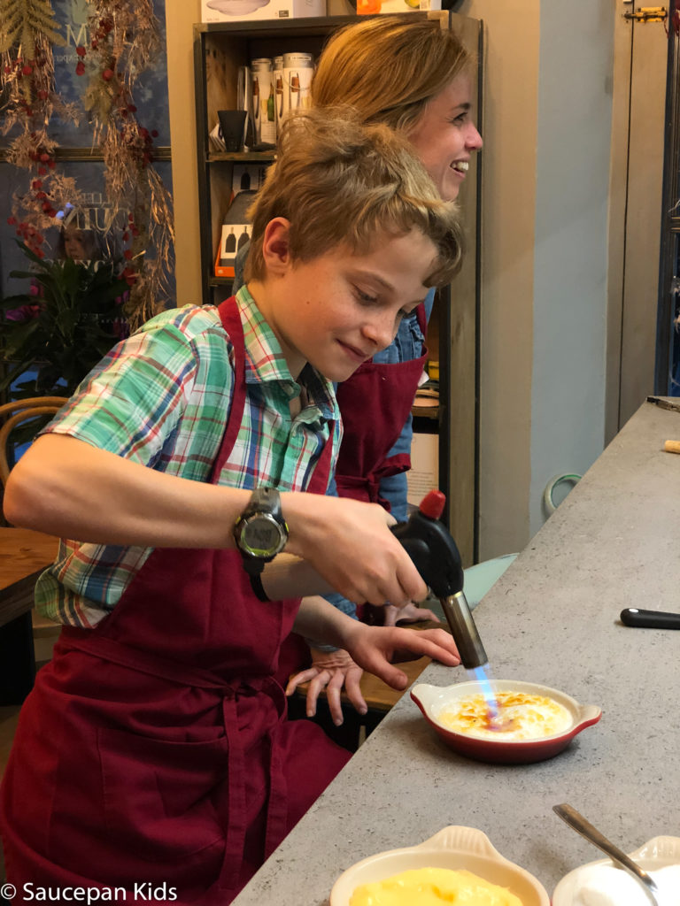 Family Friendly things to do in Costa Brava with Saucepan Kids - Catalonia - Spain - A family cooking class in Girona Fraser having fun with the blow torch