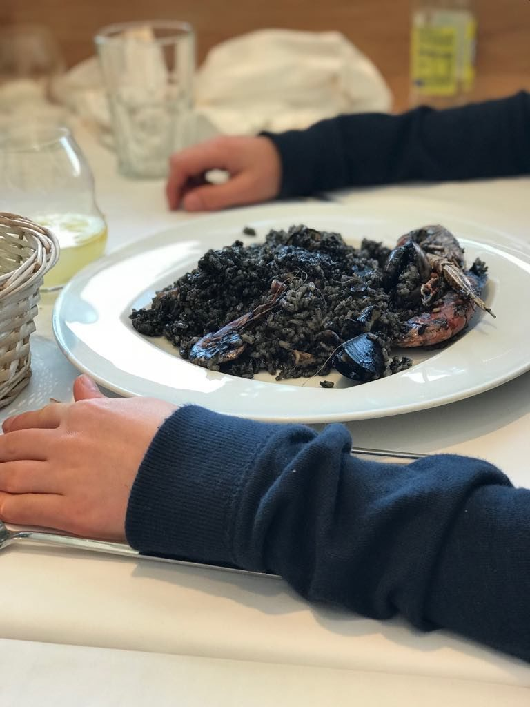 Saucepan Kids trying black squid ink seafood rice in Roses - Costa Brava Girona Top places to eat in Costa Brava